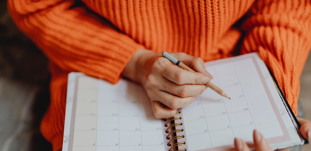 Como estudar para oab em 30 dias: mulher com calendário no colo escrevendo com um lápis