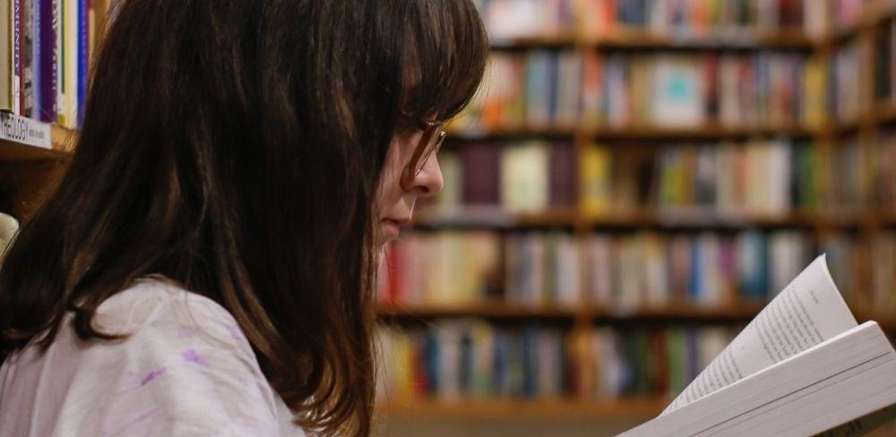 menina lendo um livro na biblioteca aprendendo como decorar leis