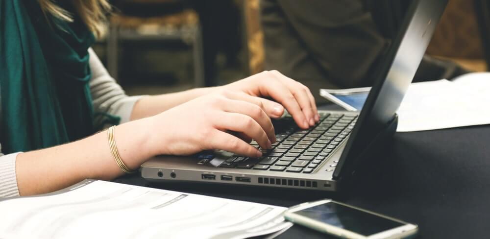 mulher escrevendo dicas OAB no notebook, com papéis e celular do lado