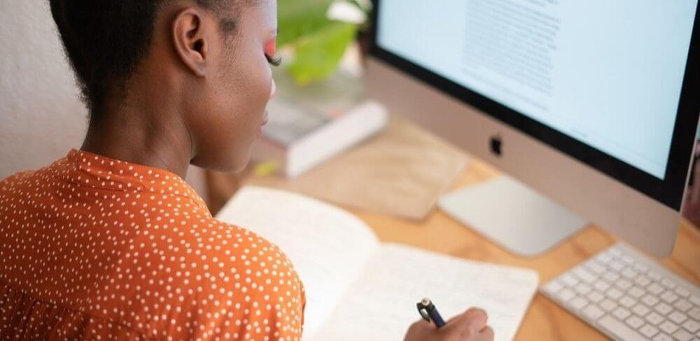 Estudar para oab: mulher sentada em uma mesa escrevendo em um caderno com um computador na frente