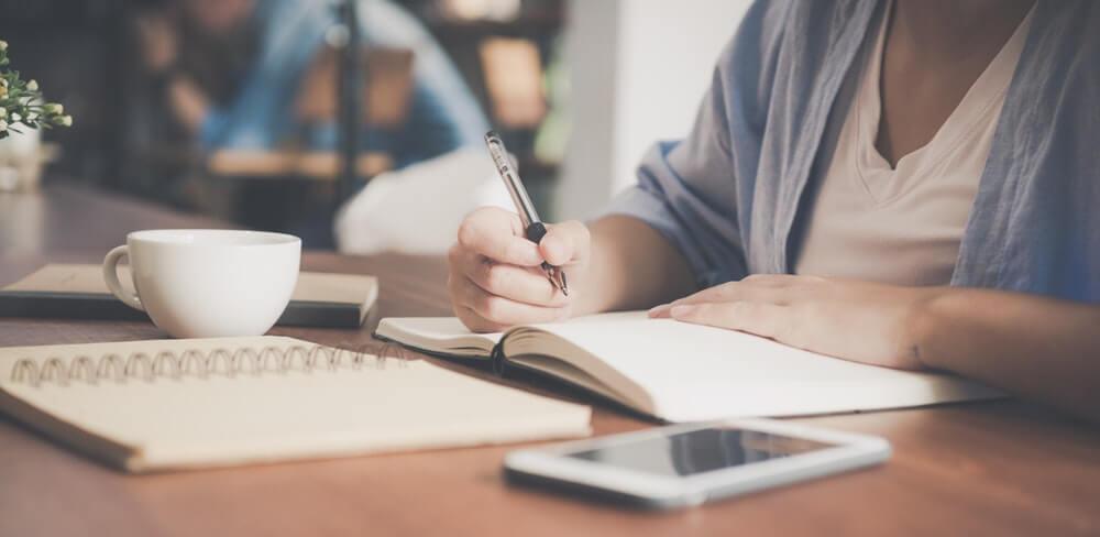 Direito administrativo OAB: mulher estudando, em sua volta tem um caderno, tablet e xícara