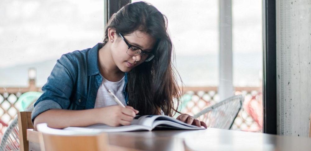 como focar no estudos: mulher estudando em uma mesa de madeira com caderno e uma caneta na mão