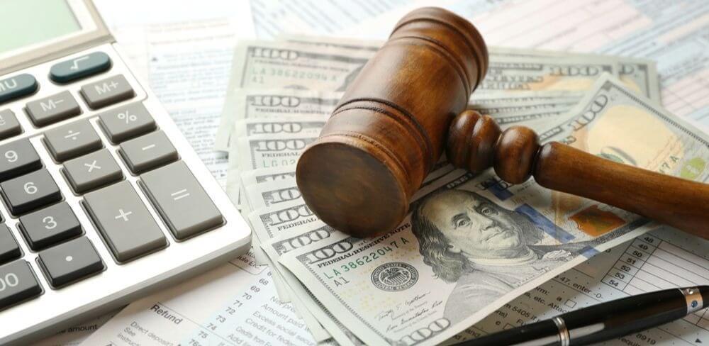 Direito Tributário OAB: notas de dinheiro, calculadora e martelo de juiz