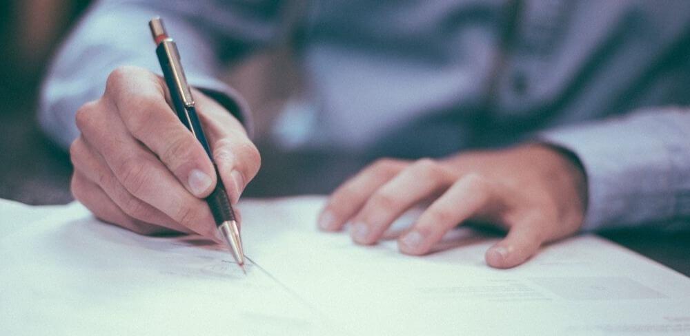 par de mãos de um homem com camisa social de cor clara escrevendo um agravo de instrumento