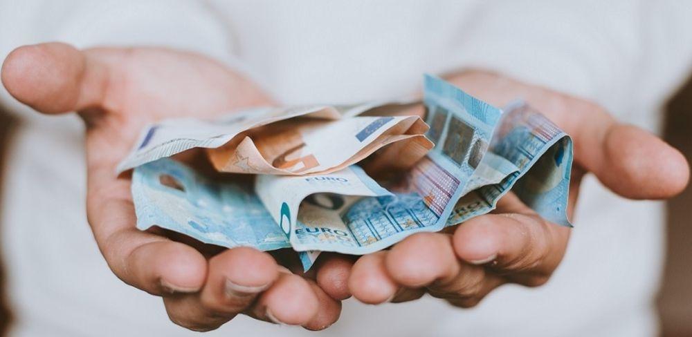 Mãos com salário e remuneração sobre elas