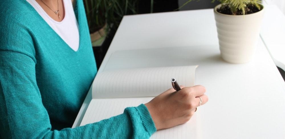 mulher escrevendo em um caderno sobre a segunda fase da OAB em Consitucional